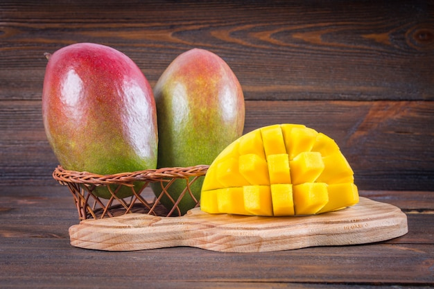Tropical fruit mango on a wooden background, whole or sliced.