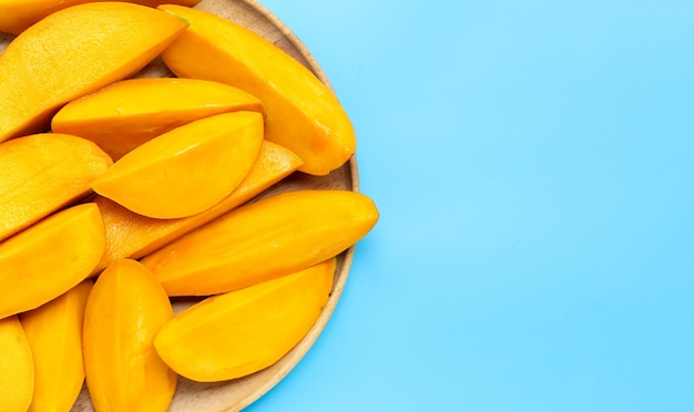 Tropical fruit, mango in wooden plate on blue background.