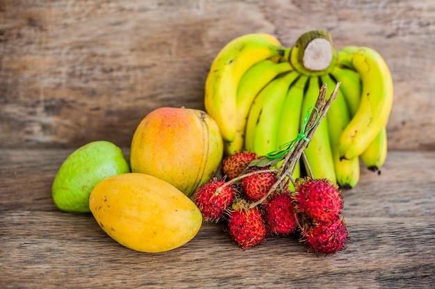 古い木製の背景にトロピカルフルーツ。ランブータン、バナナ、マンゴー、グアバ。
