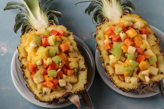 Салат из тропических фруктов в половинки ананаса на голубом фоне, крупным планом, вид сверху