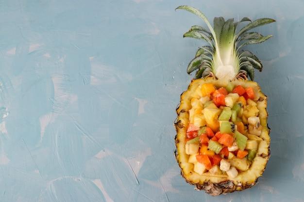 Салат из тропических фруктов в половине ананаса на голубом фоне, горизонтальная ориентация, копирование пространства, вид сверху