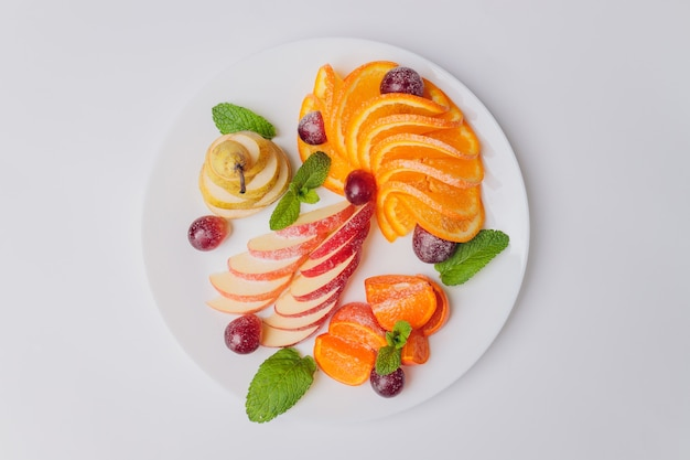Tropical fruit salad on white plate on white background photographed from above