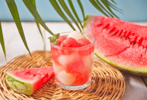 Tropical fruit salad with melon and watermelon balls in glass under the palm leaf