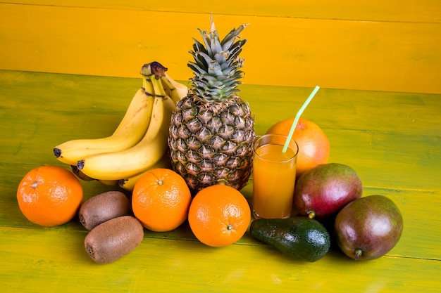 Tropical fruit on yellow wooden background, fresh food.
