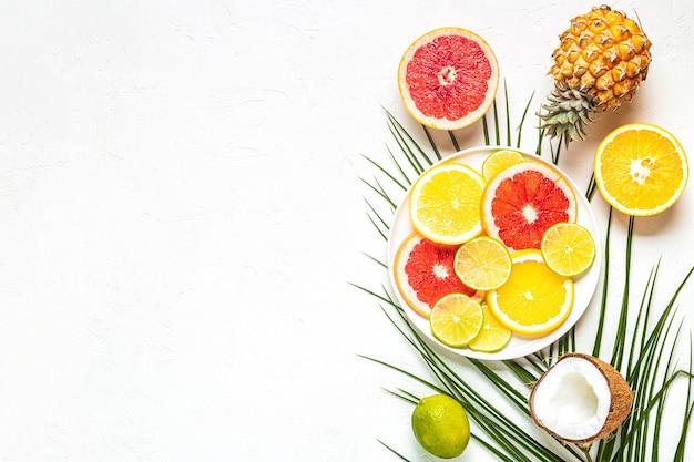 Тропические фрукты и пальмовые листья на белом фоне, вид сверху.