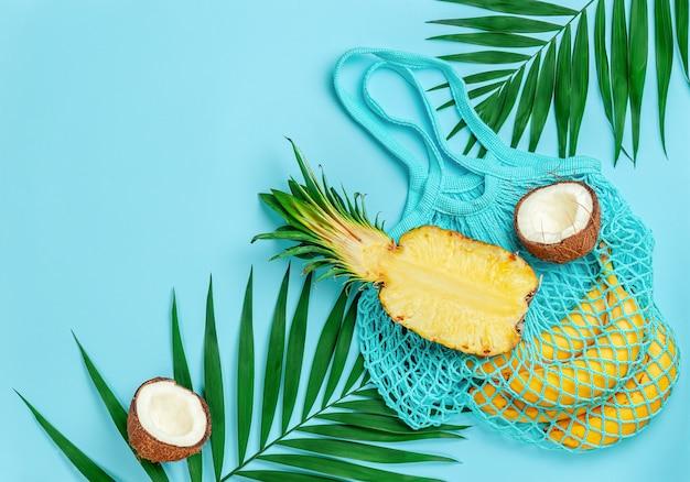 青い夏の背景にトロピカル フルーツと再利用可能な綿のバッグ。コピー スペース、オーバーヘッド。