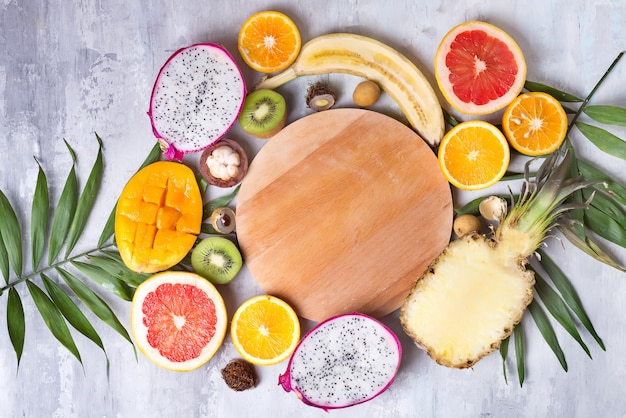 Tropical fruits assortment with wooden plate for copy space on a stone light background pattern. top view.
