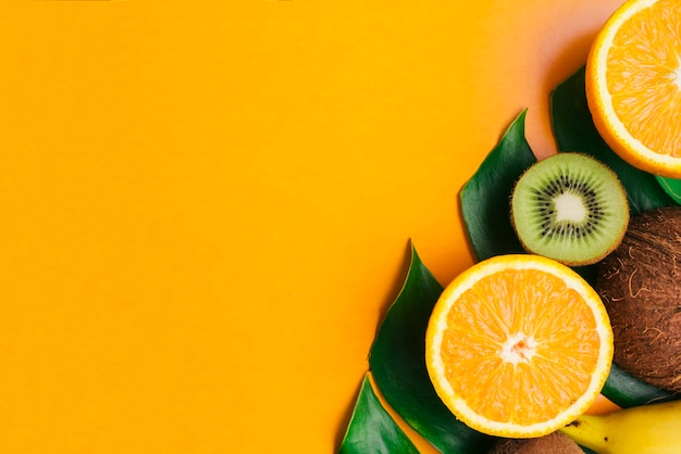 Tropical fruits background with copyspace with fruits on leaf and copyspace
