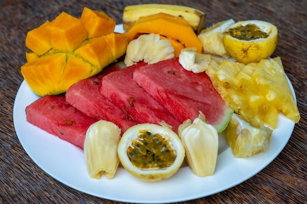 Tropical fruits on a breakfast plate, close up, top view