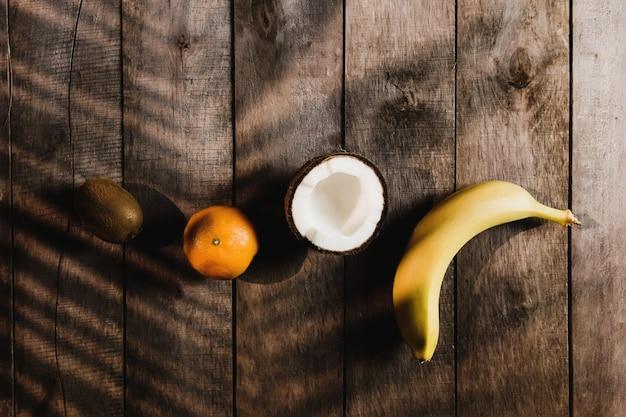 トロピカルフルーツ:ヤシの葉の影と茶色の木製の背景に壊れたココナッツ、キウイ、みかん、オレンジ、バナナ。白いココナッツパルプ。高品質の写真