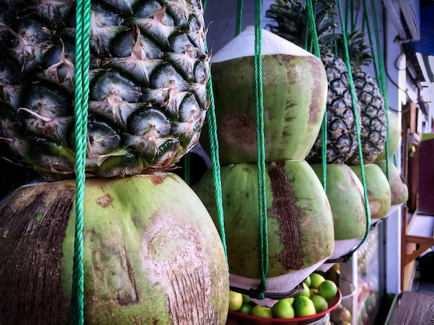 Tropical fruits hanging in front of beverage juice store