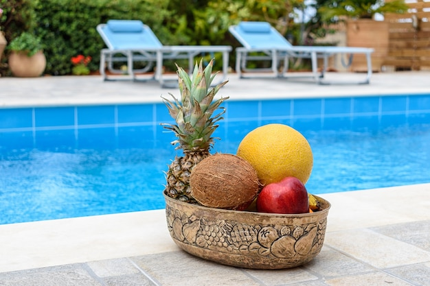 Тропические фрукты лежат в корзине на фоне бассейна