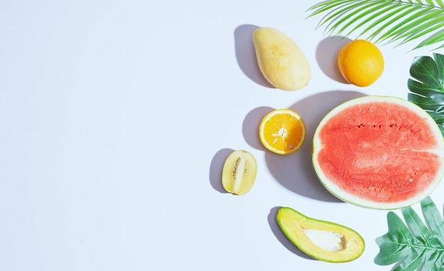 マンゴー、オレンジ、スイカ、アボカドなどのトロピカルフルーツが白い背景に配置されています
