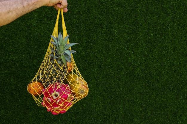 열대 과일: 망고, 파파야, 파인애플, 용 및 패션 과일이 노란색 쇼핑 섬유 가방에 녹색 배경, 수평 방향, 복사 공간