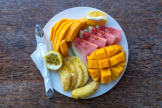 朝食プレートのトロピカルフルーツ、クローズアップ。新鮮なスイカ、バナナ、パッションフルーツ、パイナップル、ジャックフルーツ、マンゴー、パパイヤ、ビーチレストラン、島ザンジバル、タンザニア、アフリカで食べるためのオレンジ