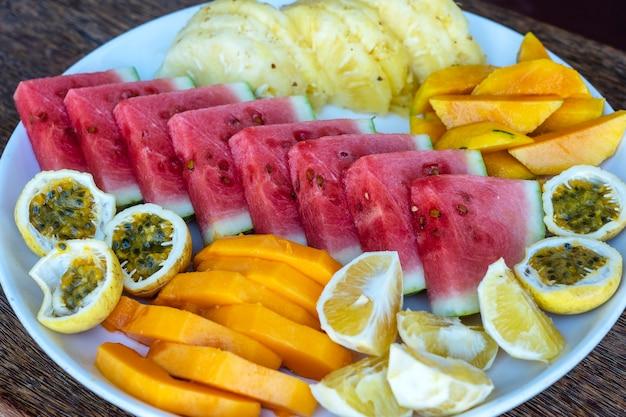 Тропические фрукты на тарелке для завтрака, крупным планом, вид сверху. свежий арбуз, маракуйя, ананас, манго, папайя, апельсин для еды в пляжном ресторане, остров занзибар, танзания, африка