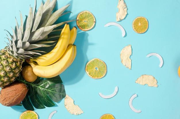 열대 과일. 파인애플. 코코넛, 오렌지, 바나나, 건조 과일 칩 파란색 배경에. 음식 개념. 여름 열대 조성. 상위 뷰, 복사 공간.