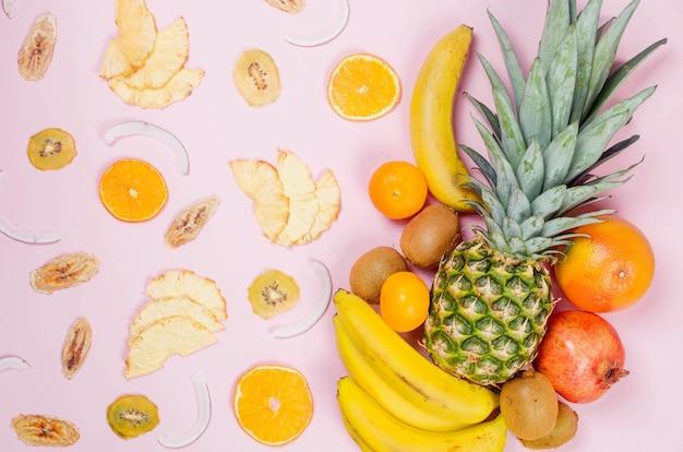 열대 과일. 파인애플. 분홍색 배경에 코코넛, 오렌지, 바나나, 건조 과일 chps. 음식 개념. 여름 열대 조성. 상위 뷰, 복사 공간.