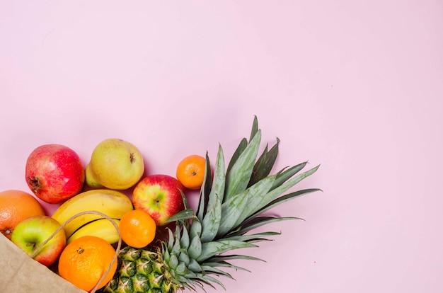 열대 과일. 파인애플. 분홍색 배경에 종이 쇼핑백에 코코넛, 오렌지, 바나나. 음식 개념. 여름 열대 조성. 상위 뷰, 복사 공간.