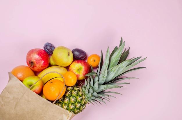 Тропические фрукты. ананас. кокос, апельсин, бананы в бумажной хозяйственной сумке на розовом фоне