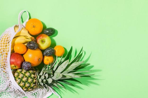 열대 과일. 파인애플. 밝은 녹색 배경에 쇼핑백에 코코넛, 오렌지, 바나나. 음식 개념. 여름 열대 조성. 상위 뷰, 복사 공간.