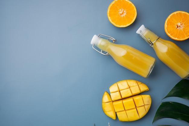 열대 과일, 파인애플, 망고, 오렌지 세트, 파란색 질감 여름 배경, 상위 뷰 평면 누워, 텍스트 복사 공간