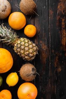 열대 과일, 파인애플, 망고, 오렌지 세트, 오래 된 어두운 나무 테이블 배경, 상위 뷰 평면 누워, 텍스트 복사 공간