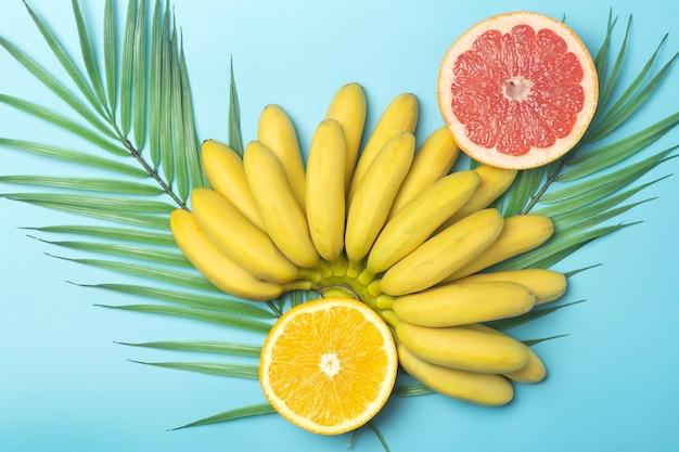 トロピカルフルーツの夏の背景。色付きの青い背景にバナナ、オレンジ、グレープフルーツ。
