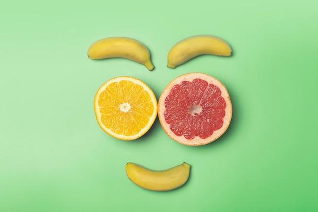 トロピカルフルーツの夏の背景。色付きの緑の背景にバナナ、オレンジ、グレープフルーツ。