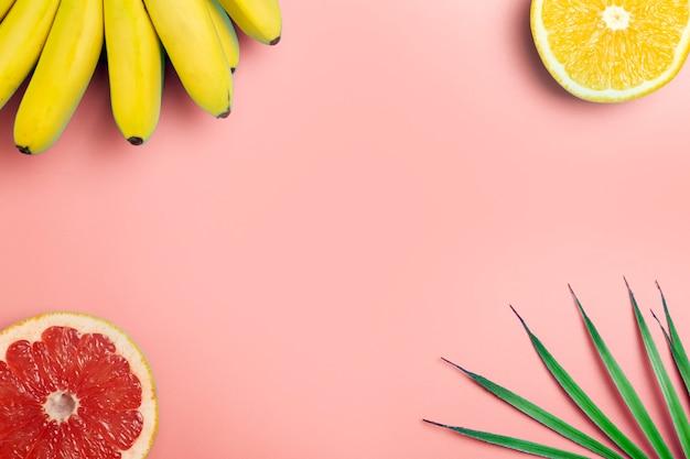 Летний фон тропических фруктов. бананы, апельсины и грейпфруты на цветном розовом фоне.