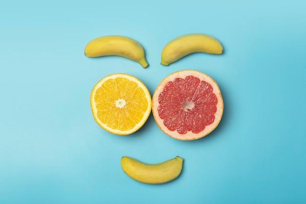 Летний фон тропических фруктов. фрукты лицо на цветном синем фоне. смузи, летние каникулы, солнце и концепция витаминов.