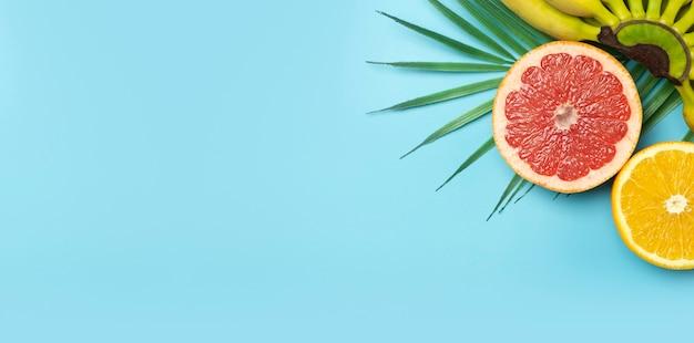 トロピカルフルーツの夏のバナーの背景。色付きの青い背景にバナナ、オレンジ、グレープフルーツ。