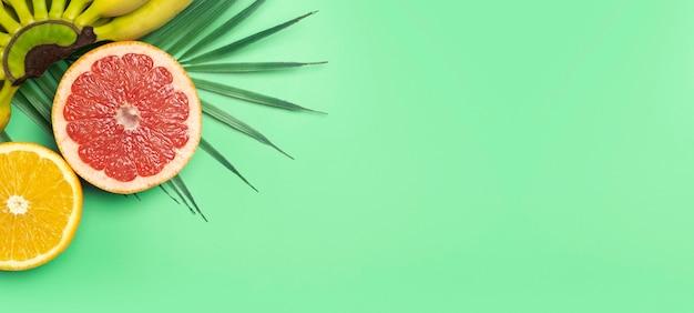 トロピカルフルーツの夏のバナーの背景。色付きの緑の背景にバナナ、オレンジ、グレープフルーツ。