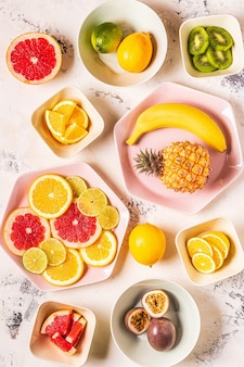 Tropical fruits whole and slices on plates