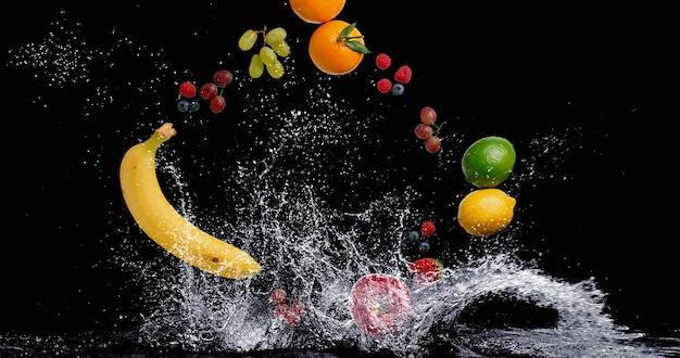 黒の背景に水しぶきと水に落ちるトロピカルフルーツ