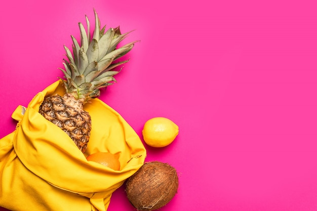 Tropical fruits with a yellow cotton bag on a pink background.