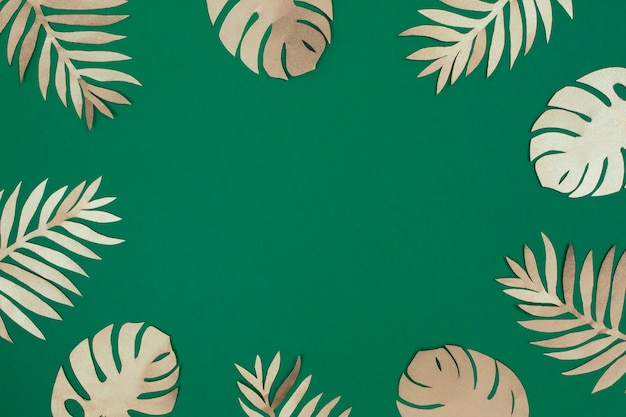 Тропические золотые бумажные листья на зеленом