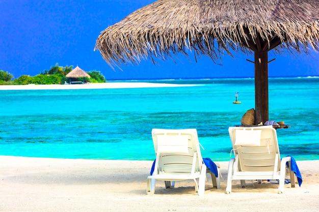 Тропический отдых - мальдивы. twp beach chaors под зонтиком на пляже