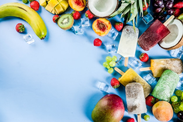 Tropical ice cream popsicles with chia seeds and fruit juices - pineapple, orange, mango, banana, kiwi, coconut, grapes, peach, strawberry
