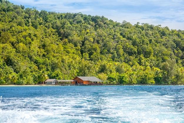 Тропический остров в индонезии. деревянная хижина и пирс у берега. водная пена за кормой яхты
