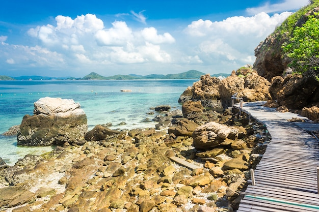 Tropical island rock and wood bridge on the beach with blue sky.
