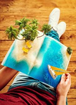 Тропический остров с пальмами и шезлонгами на странице раскрытого журнала в руках