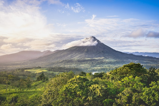Tropical landscape with a volcano rolled by a cloud