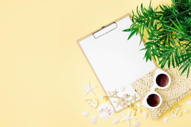 熱帯の葉、クリップボード、黄色の背景のモックアップにサングラス、上面図