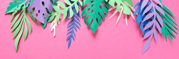 Tropical leaves cut from paper on pink.