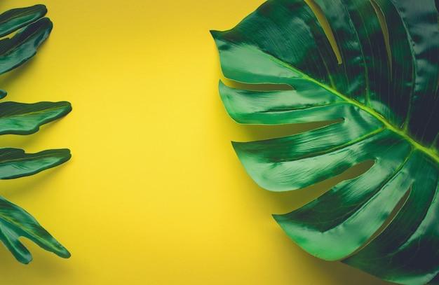 熱帯の葉が黄色いテーブルの上に横たわっています。ホームオフィス、ワークスペースデザインの背景、フラットレイ、上面図