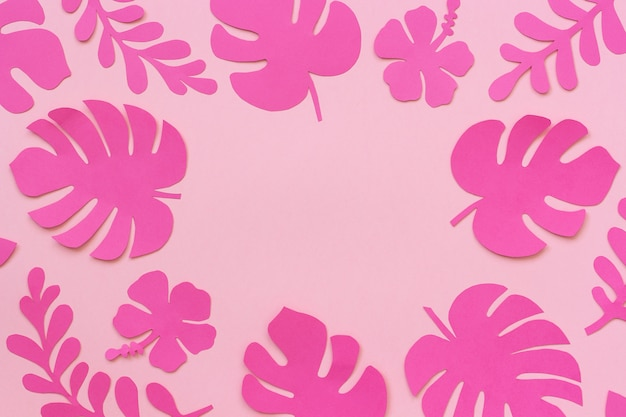 Tropical leaves of paper with copy space for your design or lettering text on pink background.