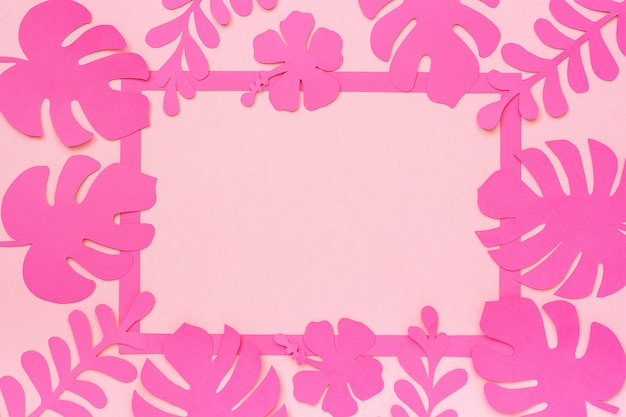 Tropical leaves pattern trendy tropical leaves of paper, frame on pink background, creative paper art