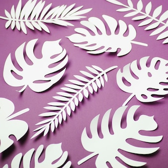Tropical leaves pattern. various paper leaves on green background. paper art. flat lay, top view