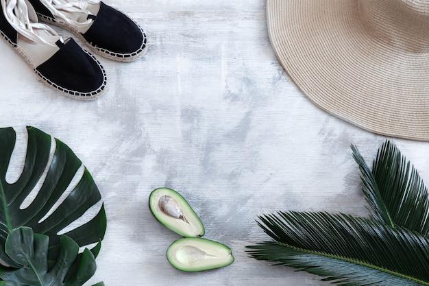 Foglie tropicali su uno sfondo bianco con accessori estivi concetto di vacanze estive e ricreazione. banner poster, modello di cartolina.